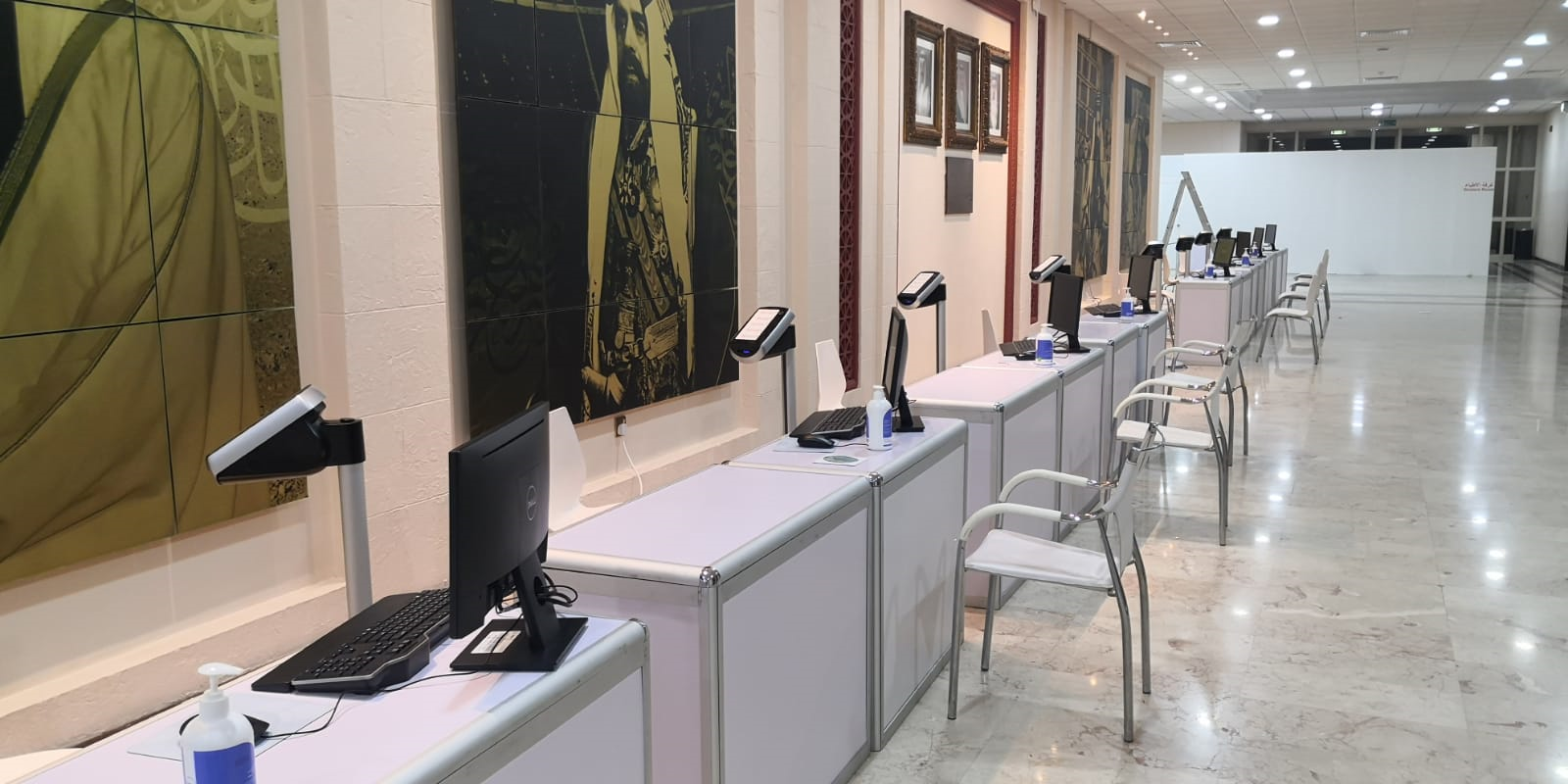 row of desks in a room with kiosks