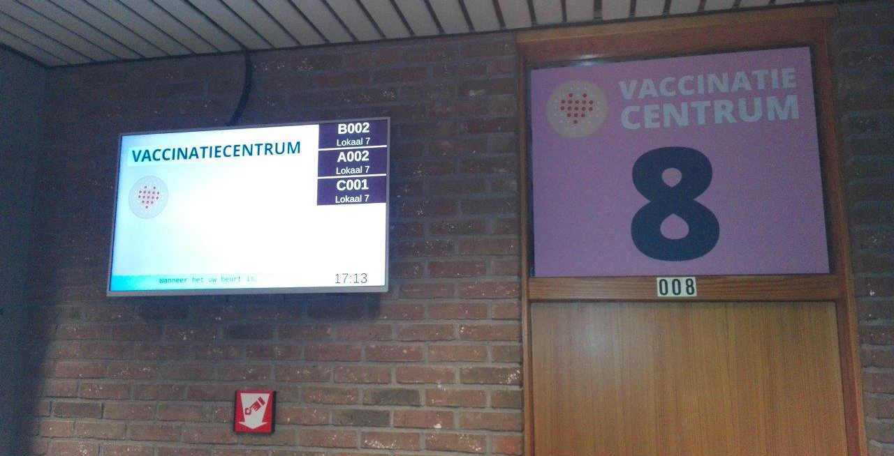 From the vaccination center in Ninove, Belgium: A tv screen showing queuing information and the door to vaccination booth nr 8.