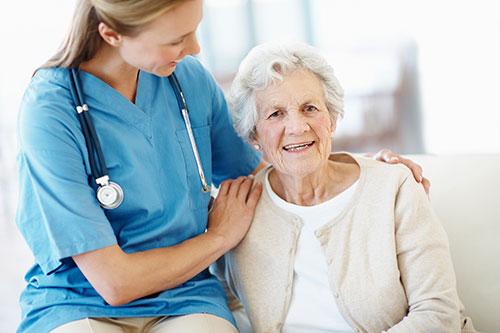 kvinnlig sjuksköterska håller om äldre kvinnlig patient