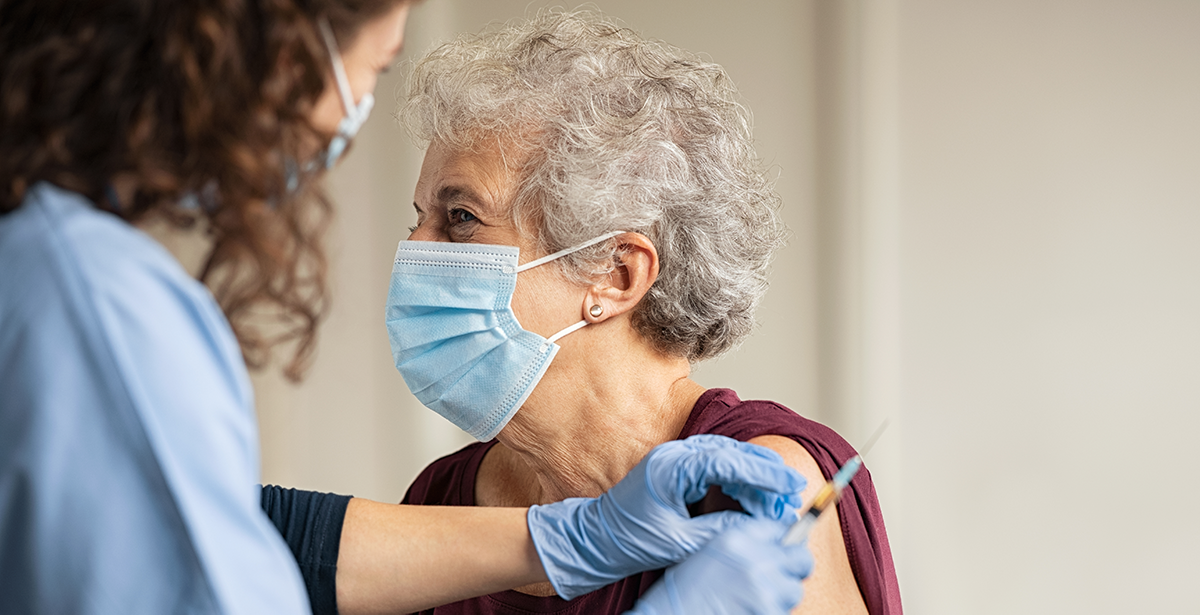 An elderly woman getting a vaccine injection from a nurse. Both are wearing face masks.