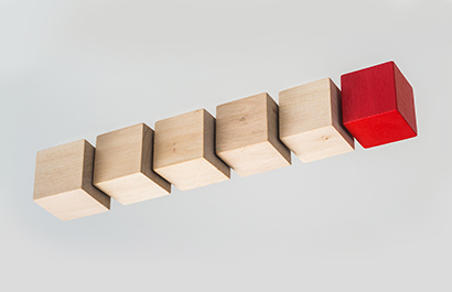 five wood blocks and one red block in a row suspended in air