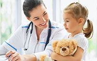 Female nurse smiling at young girl holding a teddybear