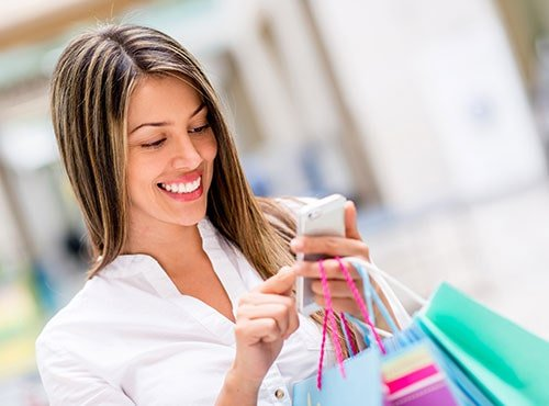 Smiling woman holding smartphone and shopping bags