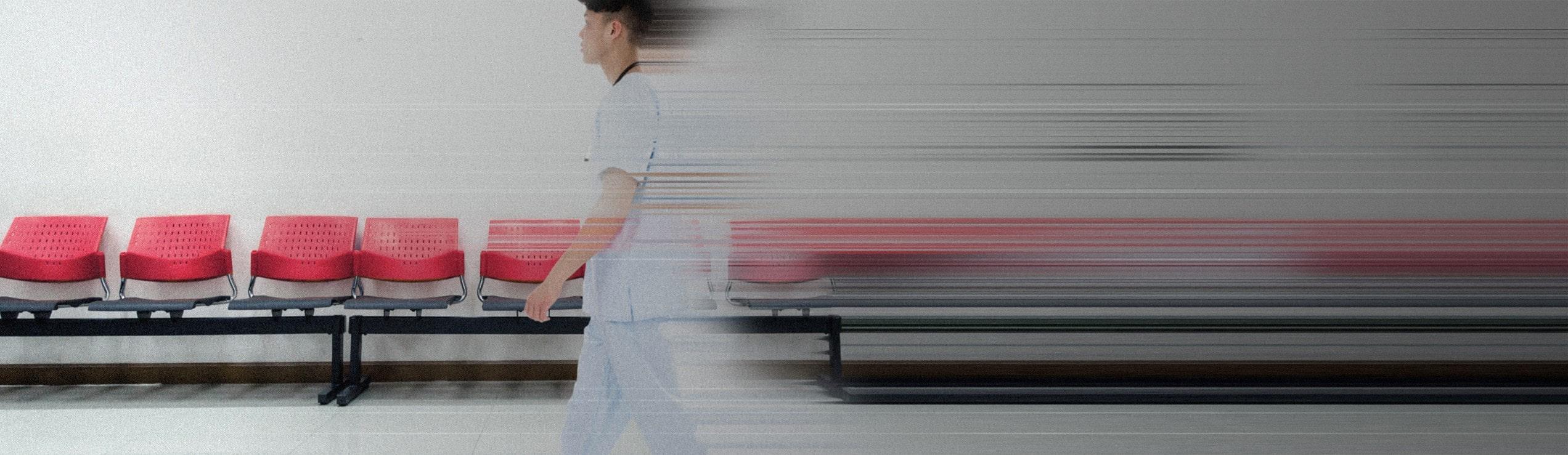 manlig sjuksköterska går i en sjukhuskorridor