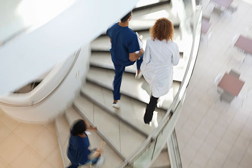 sjukhuspersonal går upp för spiraltrappa