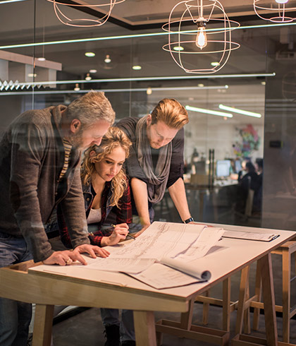 two middle aged men and one young woman standing over desk filled with blue prints
